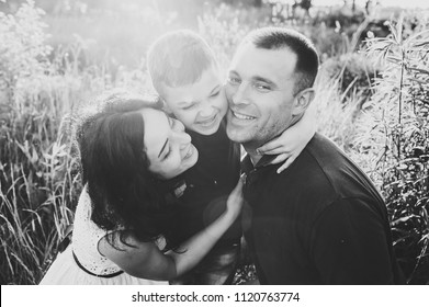 Happy young family spending time together outside in nature on vacation outdoors. Mom, dad and son sit in the grass. The concept of family holiday. Black and white photo.