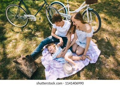 Happy young family spending time together outside. Father mother and their child in  the green park.on a picnic