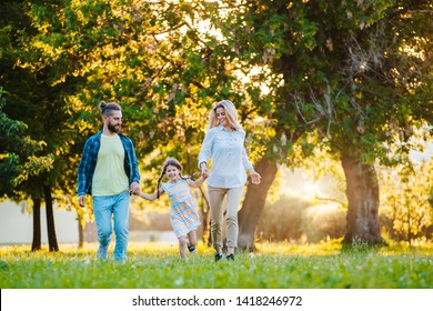 Happy young family spending time together outside in green nature. Parents, childhood, child, care, daughter, father, mother