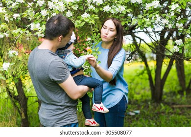 Happy young family spending time together in green nature.