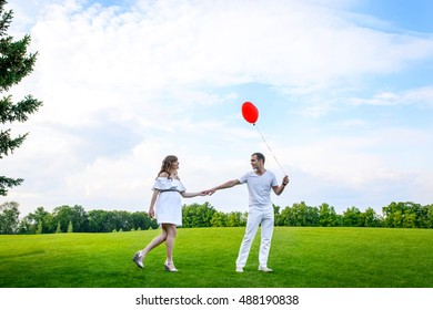 happy young family spending time in the park outdoors,man and woman in the park on a background of blue sky