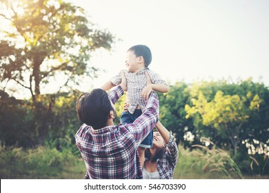 Happy young family spending time together outside in green nature park. Family love concept.