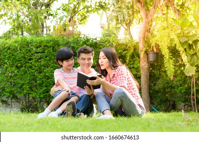A happy young family spends time playing together in the garden at the front of house the vacation.