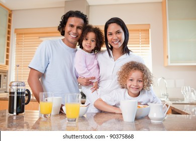 Happy young family standing in the kitchen together