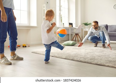 Happy young family staying at home, having fun together and engaging their small kid in sport games. Dad with little son playing soccer with inflatable ball in cozy living-room