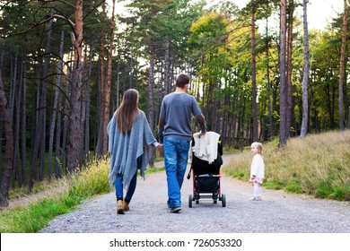 Happy young family taking a walk in a park, back view. Family holding hands walking together along forrest path with their daughter, father pushing the pram