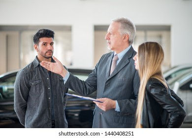 Happy young family talking to the salesman and choosing their new car in a showroom