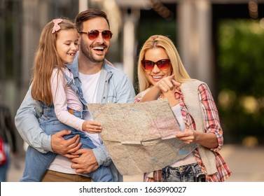 Happy young family of three smiling while spending time together.They are going on vacation.People,love,family and travel concept.