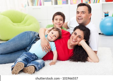 Happy young family together with two kids laying on the floor