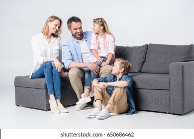 Happy young family with two children sitting together on sofa and smiling