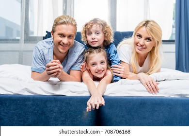 happy young family with two children smiling at camera while lying together in bed