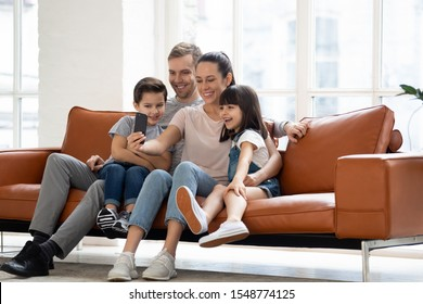 Happy young family with two kids sit on couch making self-portrait picture on smartphone together, smiling parents and children have video call use fast unlimited wireless internet connection on cell