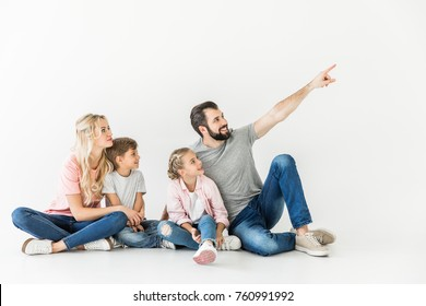 happy young family with two kids sitting together and looking away isolated on white