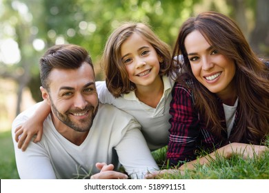 Happy young family in a urban park. Father, mother and little daughter laying on grass.
