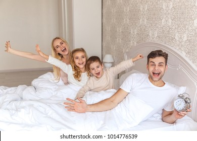 happy young family waking up together with alarm clock