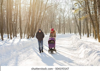 Happy young family walking in the park in winter. The parents carry the baby in a stroller through the snow.