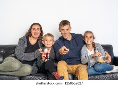 Happy young family watching TV in living room together on the sofa with chips and remote control