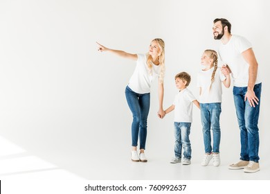 happy young family in white t-shirts holding hands and looking away isolated on white
