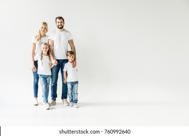 happy young family in white t-shirts and denim pants looking at camera isolated on white
