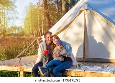 Happy young family wraps a blanket over themselves while sitting near canvas bell tent outdoors during sunset. Young mother and father hug a kid while sitting on a terrace near tent in forest