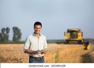 Happy young farmer engineer with notebook standing on wheat field while combine harvester working in background
