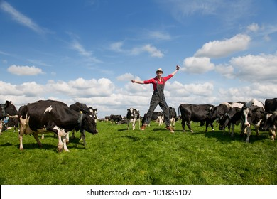 Happy young farmer jumping in field with cows