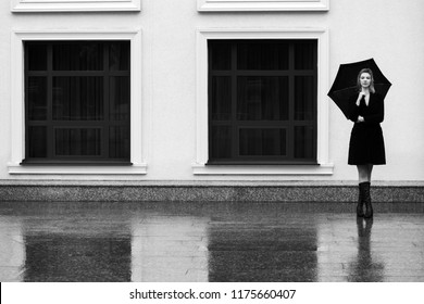 Happy young fashion blond woman with umbrella walking in city street Stylish female model wearing classic black coat