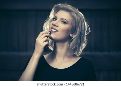 Happy young fashion blond woman in black dress with lipstick on city street