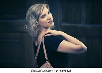 Happy young fashion blonde woman walking on city street Stylish female model in black dress with beige leather shoulder bag