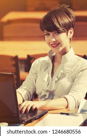 Happy young fashion business woman using laptop at sidewalk cafe Stylish female model in white shirt with pixie hair