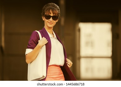 Happy young fashion business woman in sunglasses walking on city street Stylish female model with up do hair style in purple blazer and pink pencil skirt
