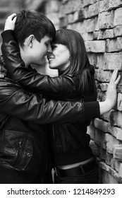 Happy young fashion couple at the brick wall  Stylish teen model in black leather jackets outdoor