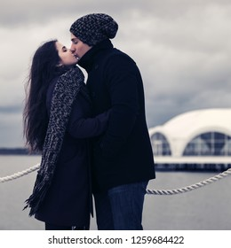 Happy young fashion couple in love kissing outdoor Stylish man and woman wearing classic coats beanie and scarf