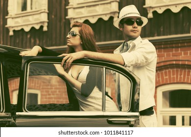 Happy young fashion couple outside a vintage car. Stylish male and female model in sunglasses