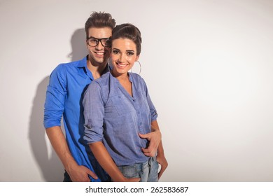 Happy young fashion couple smiling at the camera while embracing, on studio background.