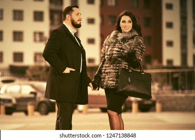 Happy young fashion couple walking on city street Stylish trendy man and woman wearing fox fur jacket and classic black coat