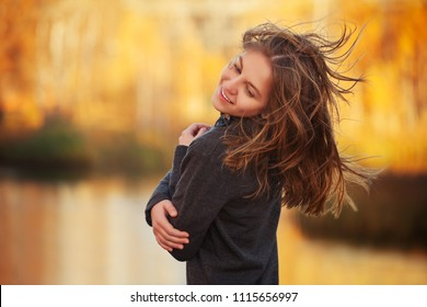 Happy young fashion girl in black pullover walking outdoor Stylish teen female model with brown straight hair