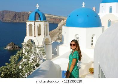 Happy young fashion model in Santorini. Beautiful tanned woman with sunglasses enjoying Oia small town in Santorini touristic island, Greece, Europe.
