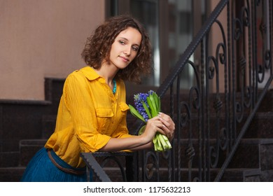 Happy young fashion woman with bouquet of flowers leaning on railing Stylish female model with curly hairs wearing yellow shirt and blue skirt