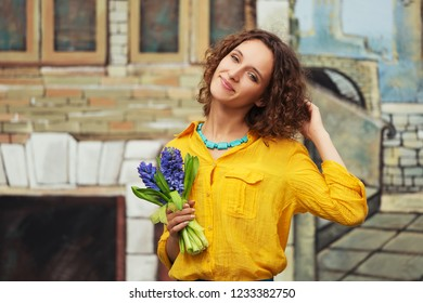 Happy young fashion woman with bouquet of flowers walking in city street Stylish female model with brown curly hairs wearing yellow shirt