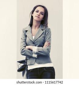 Happy young fashion woman with handbag walking in city street Stylish female model wearing grey blazer and dark blue jeans