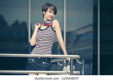 Happy young fashion woman with handbag next to mall in city street Stylish female model wearing striped tank top and mini denim skirt