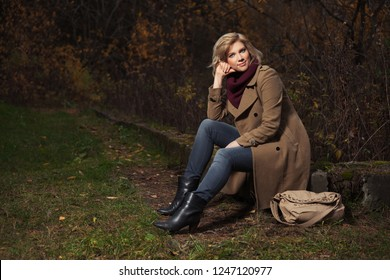 Happy young fashion woman with handbag in autumn park Stylish female model wearing classic beige coat and dark blue jeans