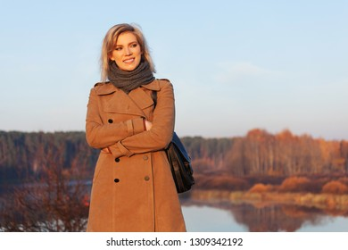 Happy young fashion woman with handbag walking outdoor Stylish female model wearing classic beige coat and scarf