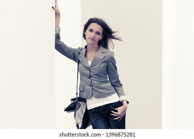 Happy young fashion woman with handbag leaning on the wall  Stylish female model in gray blazer and dark blue jeans