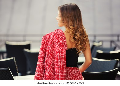 Happy young fashion woman at sidewalk cafe Stylish female model in red tweed jacket and black tank top
