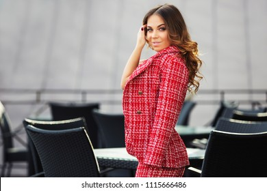 Happy young fashion woman at sidewalk cafe Stylish female model wearing red tweed jacket and skirt suit