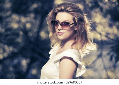 Happy young fashion woman in sunglasses walking outdoor