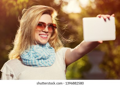 Happy young fashion woman taking selfie with digital tablet in city park Stylish female model in sunglasses and white t-shirt outdoor