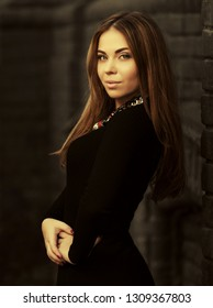 Happy young fashion woman walking on city street Stylish female model with long brown straight hairs wearing black dress